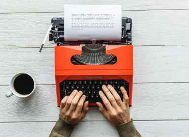 person holding black and orange typewriter